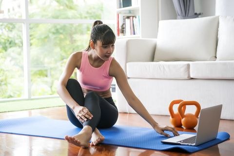 Young woman watching yoga videos at home.