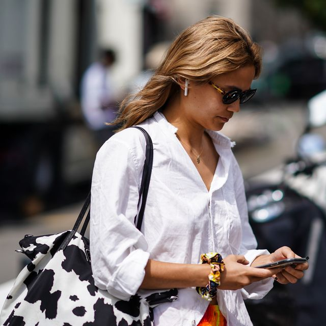 paris, france   june 19 a guest wears sunglasses, a white shirt, a black and white spotted bag, outside acne studios, during paris fashion week   menswear springsummer 2020, on june 19, 2019 in paris, france photo by edward berthelotgetty images