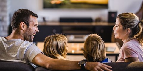 young happy parents communicating while watching a movie with their small kids in the living room