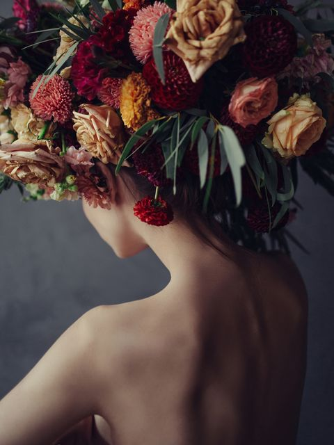 conceptual portrait of young woman wearing floral headdress