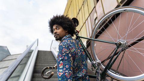 man tilt zijn fiets de trap op