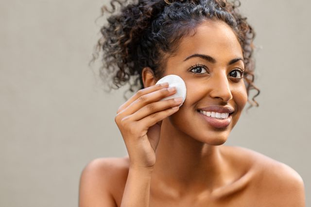 young pretty african american woman taking off her makeup with cotton wipe sponge smiling girl cleaning face with cotton pad isolated over background black young woman cleansing face, daily healthy beauty routine