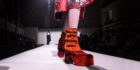 Fashion, Runway, Fashion model, Fashion show, Footwear, Red, Leg, Human leg, Shoe, Fashion design,