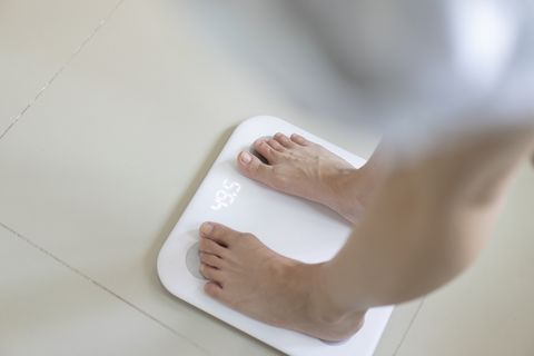 Slender female use Weight Scale for checking over weight or weight loss for good healthy