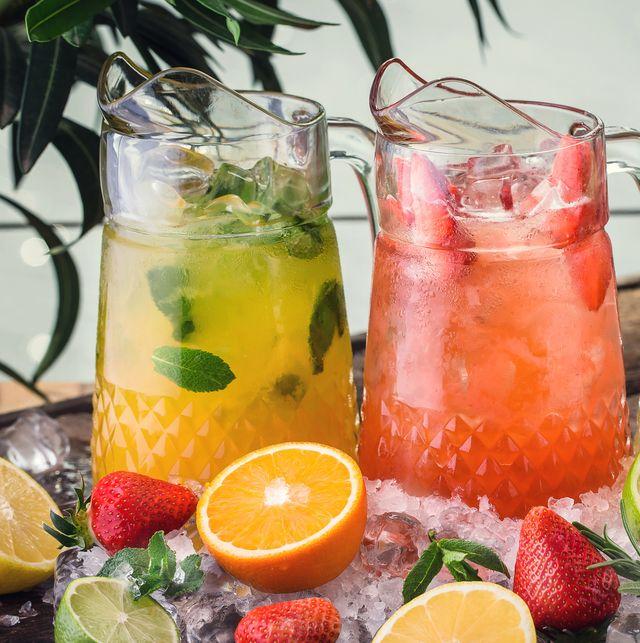 three jugs with fresh drinks from strawberry, orange and lemon juice, detox citrus water