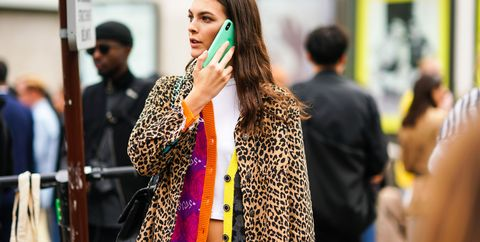 a model wears a white crop top, a purple orange and yellow grey jacket, a leopard print ripped hem jacket, adidas creamcolor sport pants, outside paco rabanne, during paris fashion week womenswear spring summer 2020