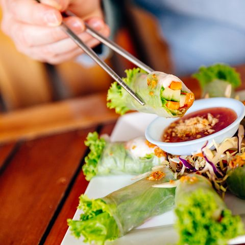 Holding fresh spring roll with chopsticks