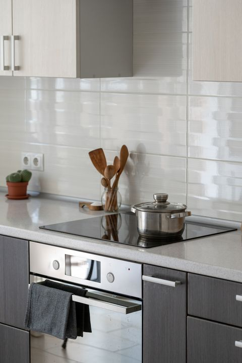ceramic induction stove with saucepan on surface, wooden supplies and green plant in flowerpot modern apartment with contemporary interior, built in oven, kitchen appliance and white tile on wall