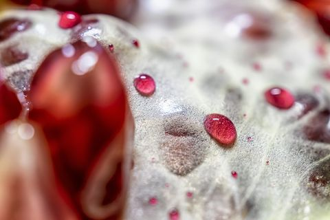 Sprinkle the pomegranate juice on the peeled pomegranate to form red water droplets.  Abstract red and yellow background.