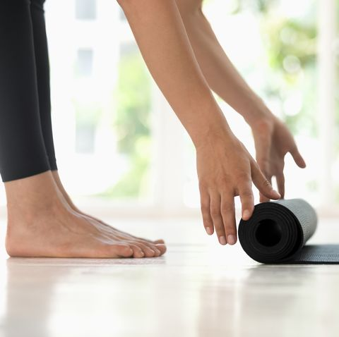 Young woman rolling black yoga mat side view close up