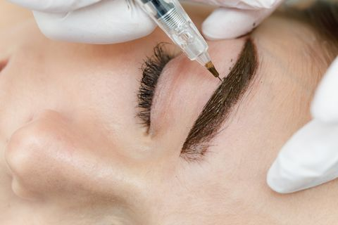 permanent makeup, tattooing of eyebrows cosmetologist in white gloves applying make up with machine for woman in beauty salon