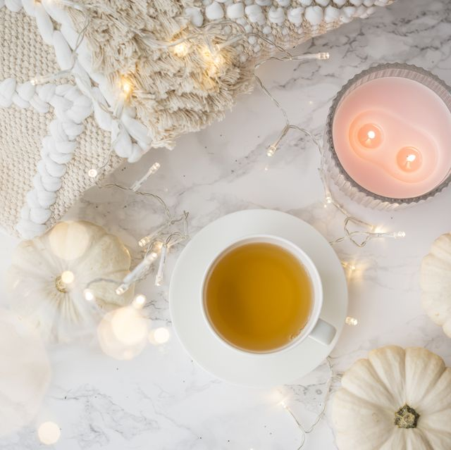 festive autumn flat lay still life with twinkling party lights and white ornamental gourds around a cup of hot tea and candles
