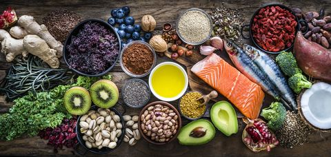 top view of healthy, antioxidant group of food shot on rustic wooden table the panoramic composition includes food rich in antioxidants considered as a super food like avocado, kale, blueberries, chia seeds, coconut, broccoli, different nuts, salmon, sardines, pollen, quinoa, hemp seeds, seaweed, cocoa, olive oil, goji berries, flax seeds, kiwi fruit, pomegranate and ginger xxxl 42mp studio photo taken with sony a7rii and zeiss batis 40mm f20 cf