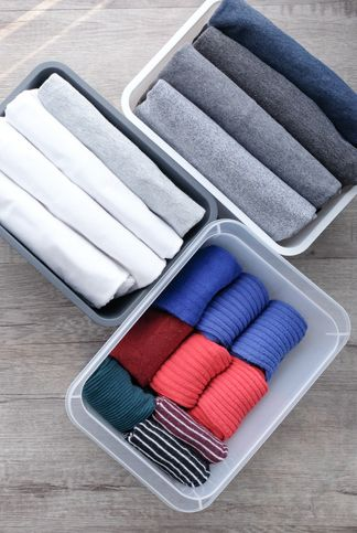 High Angle View Of Folded Clothing In Containers On Hardwood Floor