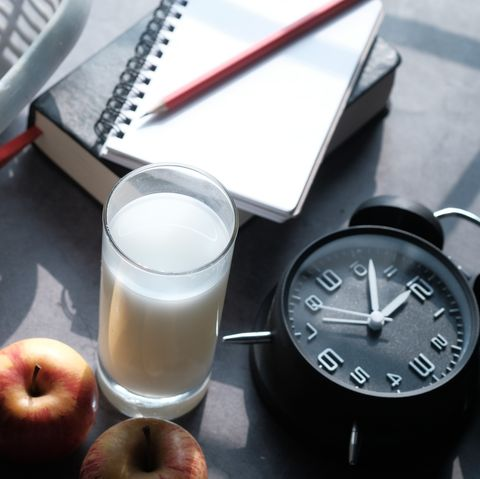 top view of fruit, milk and clock