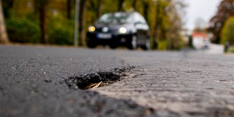 13 november 2019, north rhine westphalia, bielefeld cars drive in the schlosshofstraße in bielefeld over the heavily damaged asphalt schlosshofstrasse is currently being renovated and the residents will share in the costs since the city of bielefeld classifies the street as a residential street, the contributions for the property owners will be particularly high to dpa the bone of contention road construction contribution   pensioners anxious for old age security photo david inderlieddpa photo by david inderliedpicture alliance via getty images