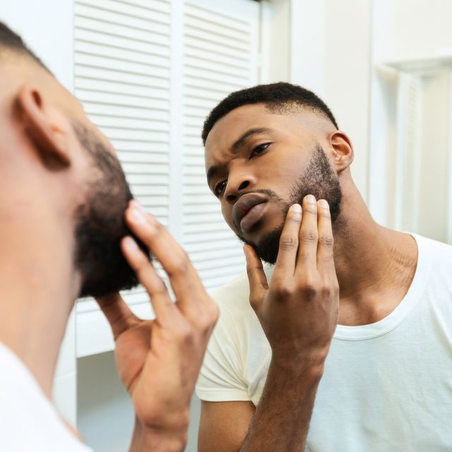 need to shave concentrated african guy looking at his beard at bathroom mirror