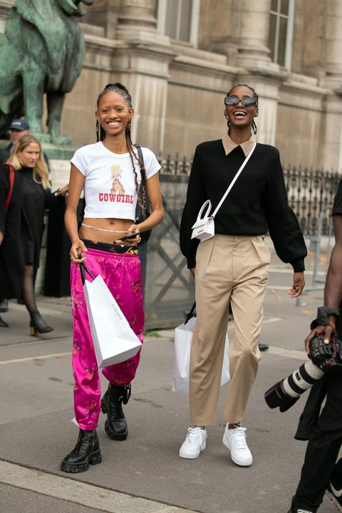paris, france   september 26  models adesuwa aighewi and tami williams  after the redemption show during paris fashion week springsummer 2020 on september 26, 2019 in paris, france adesuwa wears a cowgirl cropped t shirt, pink oriental style floral pants, and black prada combat boots tami wears black seevion sunglasses, a black top, tan polo, small white jacquemus bag, tan pants, and white sneakers  photo by melodie jenggetty images
