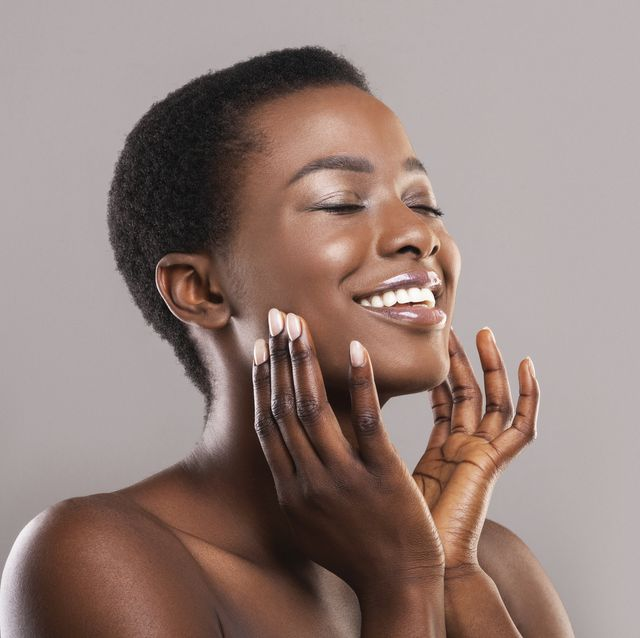 face lifting concept happy black woman with closed eyes touching soft smooth skin on her cheeks over grey background, panorama