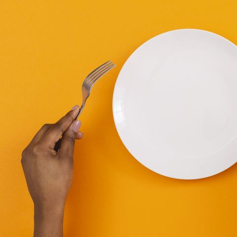 At lunchtime, an empty plate with a fork and knife in the hands of black women on an orange back, panorama