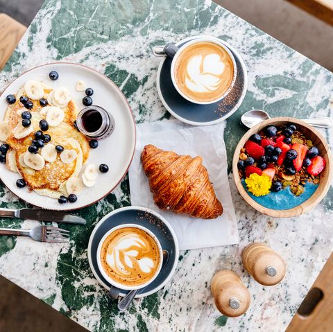 Brunch at the cafe with smoothie bowl, ricotta pancakes, croissant and cappuccino, directly above view
