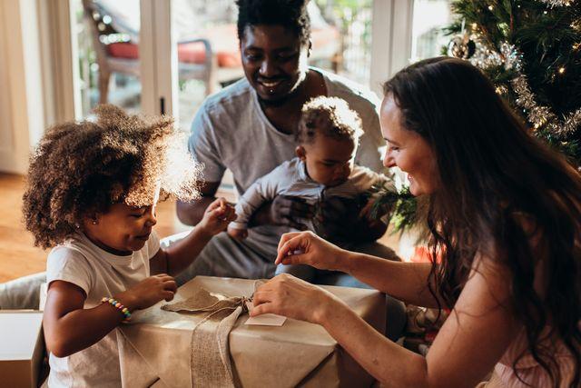 multi ethnic australian family enjoying opening presents together in their pyjamas on christmas morning