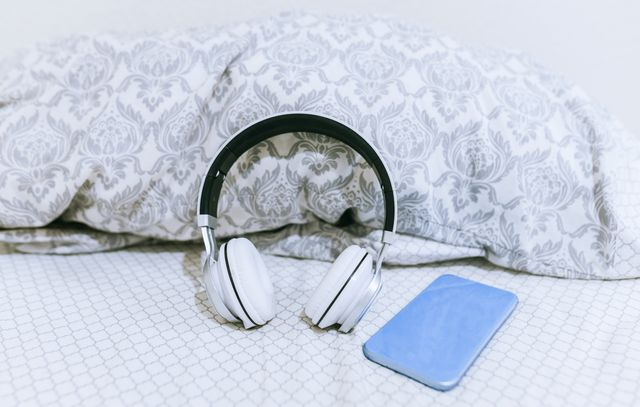 mobile phone and headphones on the bed