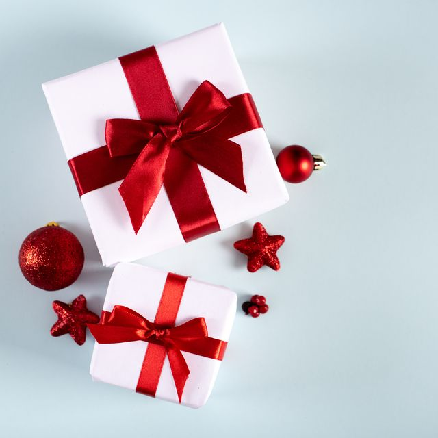 gift with red ribbon and christmas balls on blue background place under the text, banner