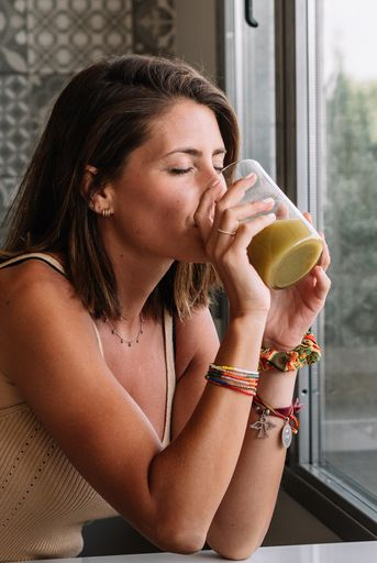 caucasian girl is having a green vegetable juice in front of her big kitchen window
