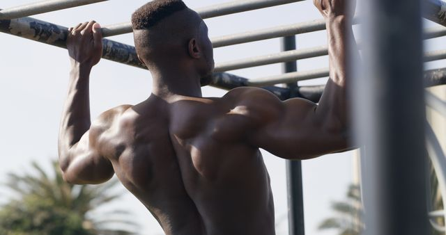 rearview shot of a muscular young man working out at a calisthenics park