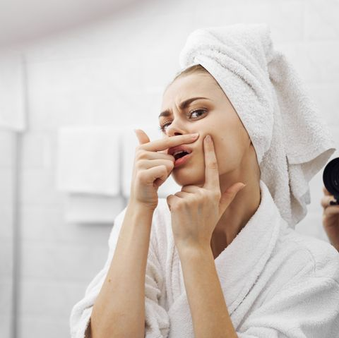 beautiful woman looks in the mirror and squeezes out a pimple facial in the bathroom