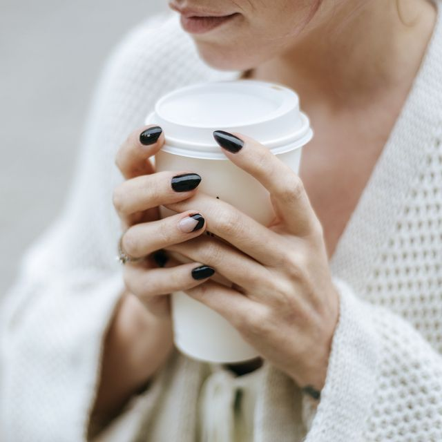 close up of womans hands with take away drink