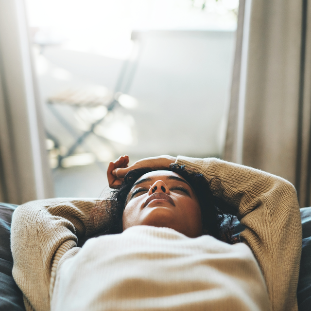 woman with dark hair and light sweater laying on bed taking a nap