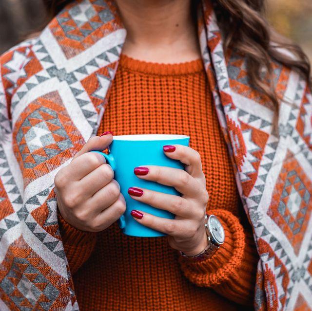woman in autumn colors holding coffee mug