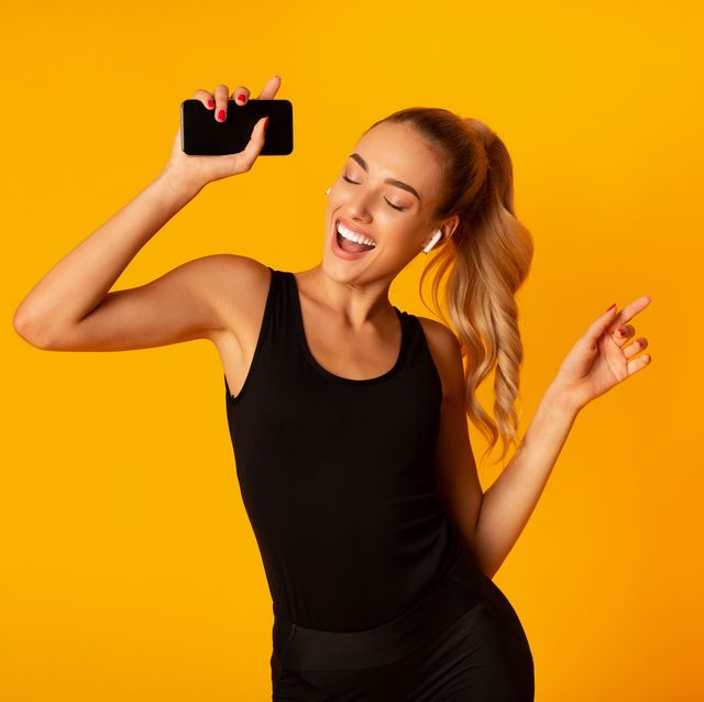 music app sporty woman in wireless earbuds holding smartphone and dancing over yellow background studio shot