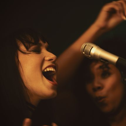 shot of two young women singing on stage in a club