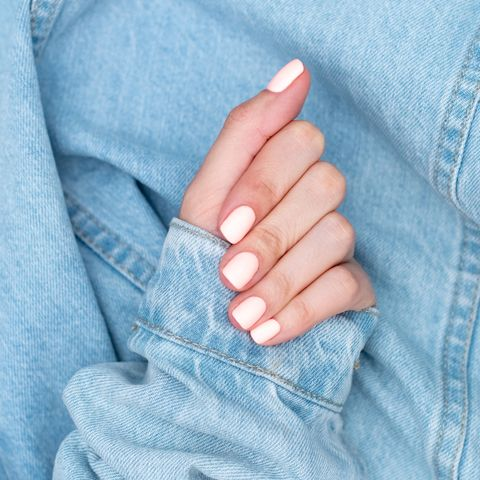 bright neon red manicure on female hands on the background of jeans nail design beauty hands
