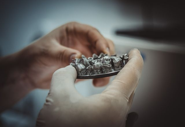 man holds in hands object printed on metal 3d printer in laboratory dental crowns created in laser sintering machine close up dmls, slm, sls technology 40 industrial revolution