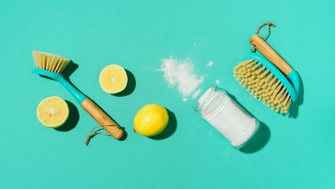 baking soda, lemon, mustard powder and bamboo brushes against household chemicals products over blue background top view copy space flat lay effective and safe house cleaning