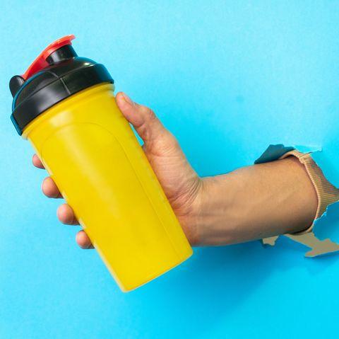 Mans fist holding protein shake, prêt à le boire, isolé sur fond bleu