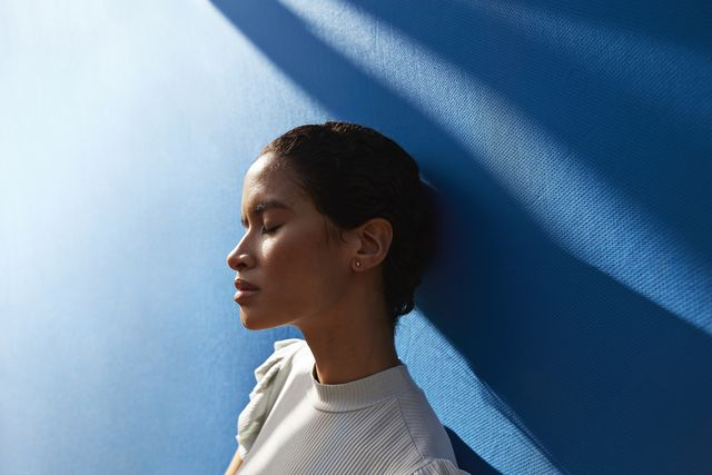 beautiful young woman standing against blue wall