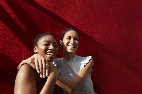 smiling young woman standing with female friend against red wall