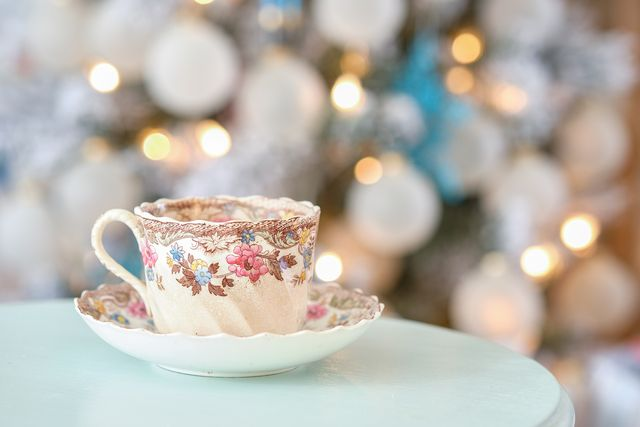 steam streams out of a colorful english tea cup on a teal table in front of a decorated christmas holiday tree