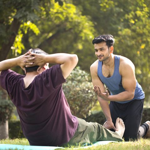 Plus size man doing sit ups exercise guided by personal trainer