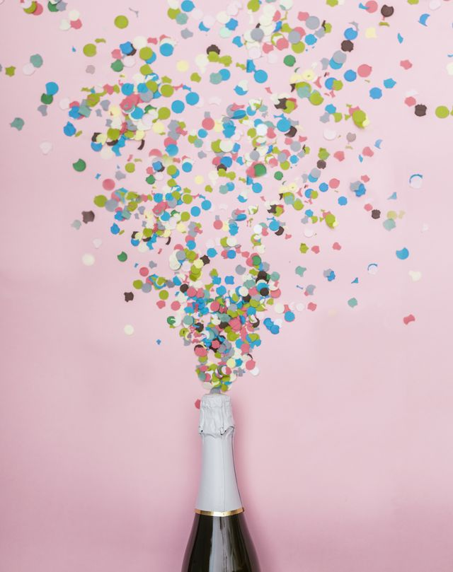 minimalist photograph of a bottle of champagne, confetti comes out of it  celebration and new year concept