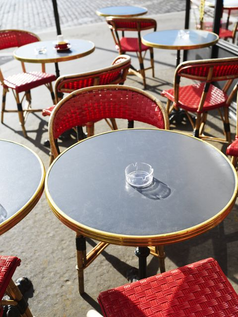 france, paris, sunlit tables and chairs outside a cafe in paris street
