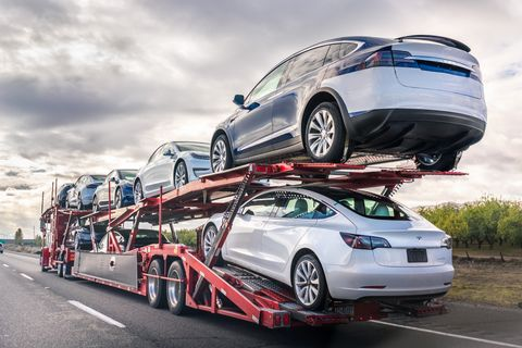 dec 8, 2019 bakersfield  ca  usa   car transporter carries new tesla vehicles along the interstate to south california, back view of the trailer