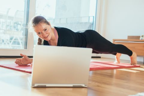 Woman doing sport in front of laptop.