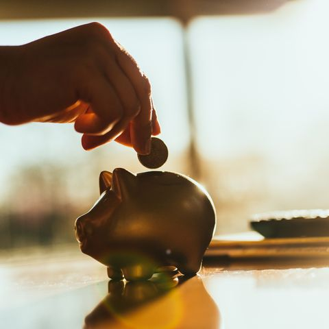 putting a coin in a gold colored piggy bank at home