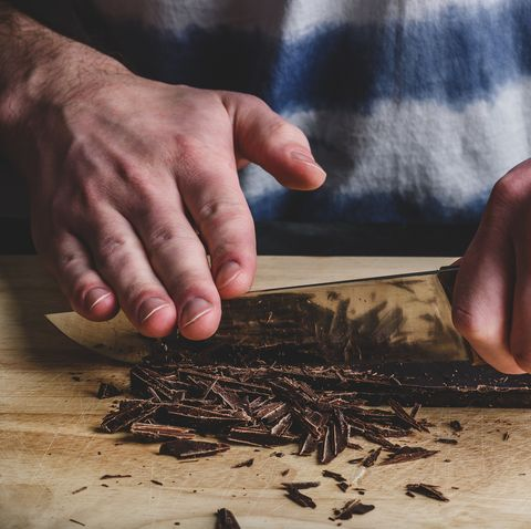 Chopping dark chocolate bar with knife